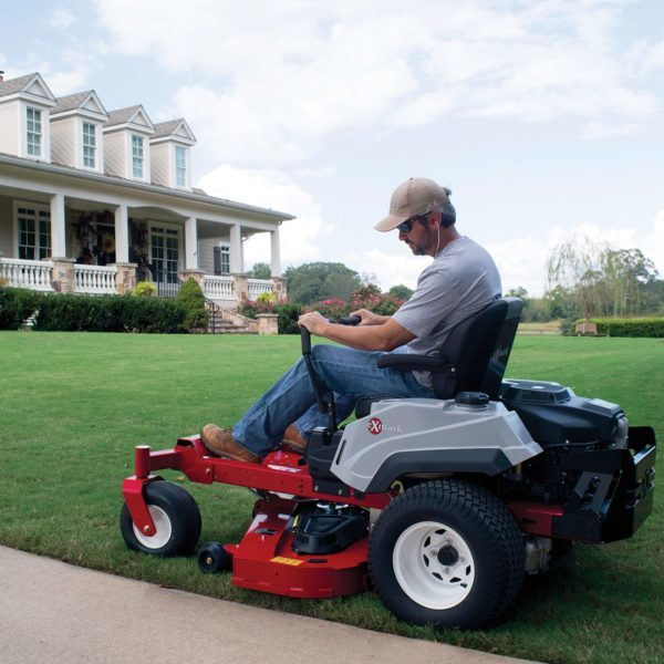 Man mowing his lawn using an Exmark 18 Quest S Series Riding Mower